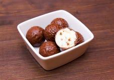 在方形的碗的巧克力果仁糖在木头 库存照片