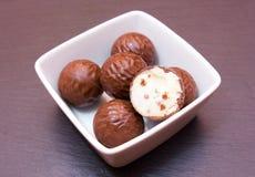 在方形的碗的巧克力果仁糖在板岩 免版税库存图片