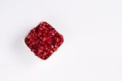 在方形的碗的石榴种子在白色背景 免版税图库摄影