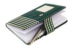 在方格的布料盖子的被打开的笔记薄有夹子和圆珠笔的 库存照片