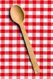在方格的桌布的木匙子 免版税库存照片