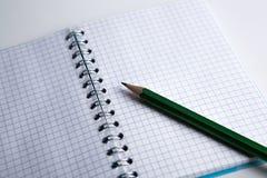 在方格的纸练习本的铅笔 免版税库存图片