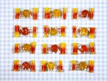 在方格的背景的五颜六色的胶粘的熊糖果 库存图片