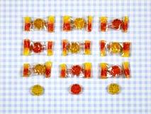 在方格的背景的五颜六色的胶粘的熊糖果 图库摄影