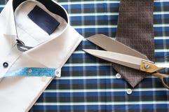 在方格的背景的白色衬衣与测量的磁带 库存图片