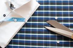 在方格的背景的白色衬衣与测量的磁带 免版税库存图片