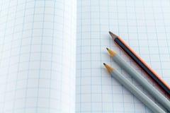 在方格的背景的铅笔 免版税库存照片