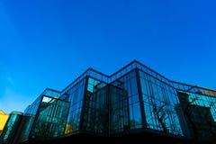 在方格的玻璃墙的上升生动的晚上太阳的反射 免版税库存图片
