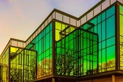 在方格的玻璃墙的上升生动的晚上太阳的反射 库存照片