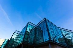 在方格的玻璃墙的上升生动的晚上太阳的反射 免版税库存照片