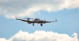在方法期间的双引擎活塞航空器登陆的在多云,晴朗的天空 免版税库存照片