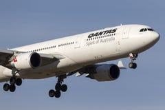 在方法的澳洲航空空中客车A330-303班机VH-QPF对土地在墨尔本国际机场 库存照片