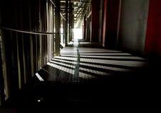 在旁边断裂的黑暗的长的走廊通过光 免版税库存图片
