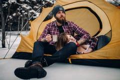 在旅游帐篷的年轻夫妇在冬天期间远足 人喝从金属杯子,女孩谎言的热的茶 库存图片