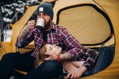 在旅游帐篷的年轻夫妇在冬天期间远足 人喝从金属杯子,女孩谎言的热的茶 免版税图库摄影