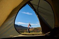 在旅游帐篷,从里边看法前面的年轻女人,在木质的小山和天空蔚蓝背景  免版税库存图片