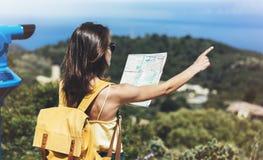 在旅行、生活方式概念冒险、旅客有背包的在背景山和蓝色海的行家旅游举行和神色地图 库存图片