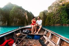 在旅行乘在海岛上的小船的爱的夫妇 免版税库存图片