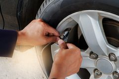 在旅行前供以人员有空气的` s手检查的和填装的轮胎 免版税图库摄影
