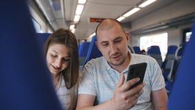 在旅行在火车的爱的一对夫妇,在看照片的舒适的椅子坐智能手机 股票视频