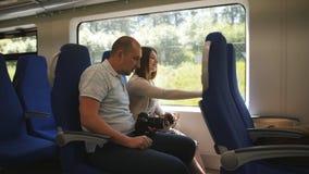 在旅行在elektro火车的爱的一对夫妇注视着通过窗口周围 股票录像