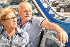 在旅行片刻的愉快的资深夫妇在观光的公共汽车 图库摄影