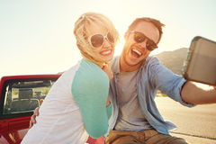 在旅行的夫妇坐采取Selfie的敞篷车汽车 免版税库存照片