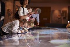 在旅行的学生到看地图和做笔记的博物馆 库存照片