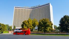 在旅馆乌兹别克斯坦的背景的红色游览车在塔什干 免版税库存照片