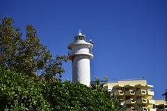 在旅馆和棕榈树中的灯塔在散步在太阳海岸的西班牙马尔韦利亚 库存图片