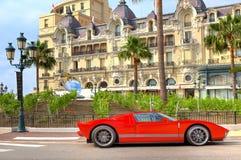 在旅馆在蒙地卡罗,摩纳哥的de巴黎前面的红色豪华汽车 免版税库存图片