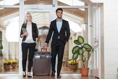 在旅馆大厅、买卖人小组人和妇女客人的企业夫妇到达 免版税库存照片