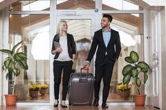 在旅馆大厅、买卖人小组人和妇女客人的企业夫妇到达 免版税图库摄影