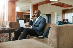 在旅馆大厅的商人使用手机 免版税库存图片
