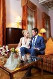 在旅馆客房内部的愉快的新娘和新郎  库存图片