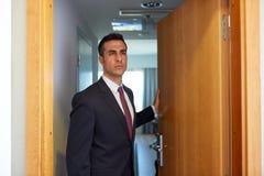 在旅馆客房或办公室门的商人 库存图片