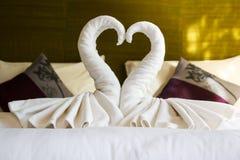 在旅馆床上的白色清洁毛巾 免版税库存图片
