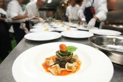 在旅馆或餐馆厨房里烹调为晚餐的厨师 免版税图库摄影
