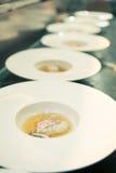 在旅馆或餐馆厨房里烹调和装饰晚餐的厨师食物 图库摄影