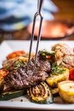 在旅馆或餐馆厨房里烹调仅手的厨师 与菜装饰的准备的牛排 图库摄影