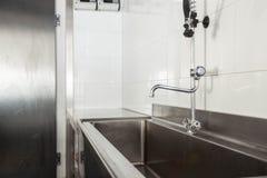 在旅馆或餐馆的厨房里清洗洗碗盘行为地区 免版税库存图片