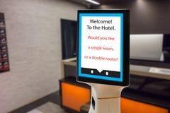 在旅馆概念,机器人男管家帮助的机器人预定的顾客和预留屋子,投入了对象,食物,辅助部件里面 库存图片