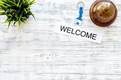 在旅馆登记 措辞在轻的木桌背景顶视图copyspace的受欢迎的近的服务响铃 免版税图库摄影