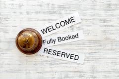在旅馆 词在轻的木台式视图copyspace欢迎,充分地预定,预留 库存照片