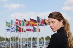 在旗子旁边的女实业家 免版税库存图片