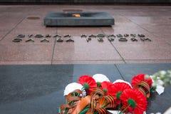 在无名战士和永恒光墓碑的花  免版税图库摄影