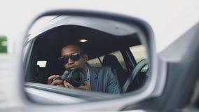 在无固定职业的摄影师旁边镜子的反射供以人员坐在汽车里面和拍摄与dslr照相机 库存照片