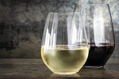 在无茎的玻璃的白色和红葡萄酒有板岩背景 免版税库存照片