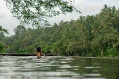 在无限水池的年轻亚洲女孩游泳有美丽的景色 免版税库存图片