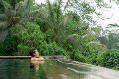 在无限水池的年轻亚洲女孩游泳有美丽的景色 免版税库存照片